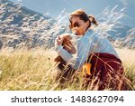 Stock photo smiling female hugs her beagle dog resting as they walking in mountains together 1483627094