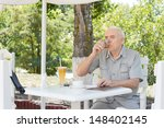 elderly man sipping a glass of...