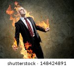 Small photo of Image of young businessman in anger burning fire