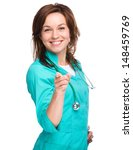 Portrait of a young attractive woman wearing doctor uniform and pointing at you, isolated over white - stock photo