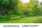 Green grass lawn in a garden with random pattern of grey concrete stepping stone , Flowering plant, shurb , trees on backyard under morning sunshine with good care landscaping in a pubblic park