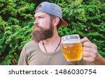 Drinking culture. Hipster holding beer mug. Bearded hipster drinking beer on summer nature. Hipster drinker. Hipster man with craft beer. Brutal man with drinking habits. Drinking only heavy beer.