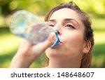 young woman drinking water | Shutterstock . vector #148648607