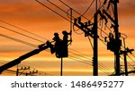 Small photo of Silhouette two electricians with disconnect stick tool on crane truck are working to install electrical transmission on power pole with blurred sunrise sky background in technology concept