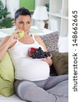 Young pregnant woman eating fresh fruits at home - stock photo