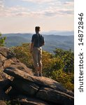Hiker standing on rock outcroppings while looking out over mountains in the late afternoon. - stock photo