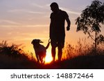 Stock photo young man with his yellow labrador retriever in nature back lit 148872464