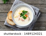 Finnish creamy soup with wild salmon, potatoes, carrots and parsley. Healthy food. Dieting. Finnish cuisine. Close up, top view