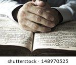 hands praying on bible   Shutterstock . vector #148970525