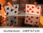 Small photo of Woman shuffling a deck of cards with a reflection of the hands and cards shown on a glass table