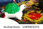 A student is painting a public domain of turtle sculpture for decoration. Arts and hand works concept image.