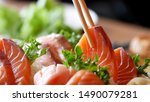 Asian people eating sashimi set in Asian restaurant. Hirame sashimi,salmon sashimi and tuna sashimi dish. Japanese food concept.