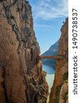 Small photo of Boardwalk and footbridge of 'Caminito del Rey' mountain walk and hiking route. Bridge between two steep mountains over the canyon and lake in the background. Path along steep cliffs. Andalusia, Spain
