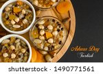 """Small photo of Traditional Turkish Dessert is Asure """"Noah's Pudding"""" on wooden plate at black surface with """"Ashura Day Turkish """"lettering."""