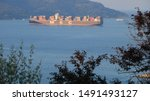 La Spezia, Liguria, Italy, about the August 2019. MSC cargo container ship departing. Olive leaves in the foreground. The Gulf in the Mediterranean Sea with Islands in the background light of dawn. - stock photo