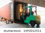 Forklift driver loading package boxes into shipping container at dock warehouse. Cargo shipment with truck. Freight truck. Industry warehouse logistics transportation.
