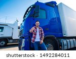 Professional truck driver in front of long transportation vehicle holding thumbs up ready for a new ride. Transportation services. - stock photo