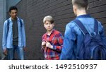 Small photo of Cruel teenagers threatening younger boy, physical intimidation, school bullying