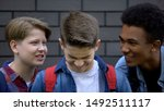 Small photo of Spiteful students teasing boy face-to-face, telling insults, emotional bullying