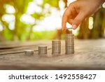 Small photo of Arrange coins into heaps with hands, content save money