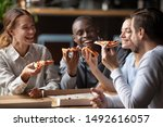 Small photo of Cheerful multiracial happy best friends couples laugh at funny joke eating pizza in cafe together, happy multicultural young mates having fun sharing food at party meeting in pizzeria sit at table