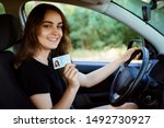 Small photo of Student in a modern car showing driving licence