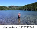 Man wading in Todd Lake, Oregon, with Broken Top in background on clear sunny summer afternoon.