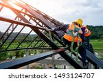 Construction worker wearing safety harness using secondary safety device connecting into 15 mm static rope using as fall restraint shingle on top of the new roof. - stock photo