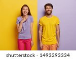 Small photo of Photo of two delighted young woman and man stand together, express good emotions, smile happily, spend free time together, have fun, pose against yellow and purple background, dressed casually
