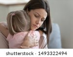 Small photo of Attractive sad woman embraces little frustrated girl rear view, daughter snuggle to mother seeking for support and protection, concept of empathy and consoling or people make peace after scold concept