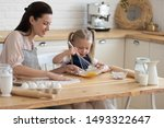 Small photo of Little girl holding whisk stirring eggs in bowl making with mommy mixture for morning pancakes, mother daughter preparing sweet pie using flour sugar milk sitting on chairs at table in modern kitchen