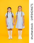 Small photo of bonded. small girls in school uniform. retro look. children in vintage style. old school. kid fashion. happy friends on yellow background. fashion beauty. childhood happiness. sisterhood concept.