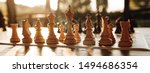 Small photo of Playing chess on a chessboard at sunset. Tactics and strategy. Black and white figures.