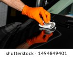 Small photo of Car polish wax worker hands polishing car. Buffing and polishing vehicle with ceramic. Car detailing. Man holds a polisher in the hand and polishes the car with nano ceramic. Tools for polishing