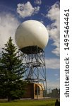 Doppler weather radar ball against blue sky with white clouds and sun reflecting off of sphere. Located at a National Weather Service site. Tree in foreground.