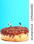 Small photo of Conceptual image of a miniature figure golfers stood on a chocolate doughnut playing a round of golf