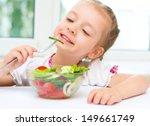 little girl eating vegetable... | Shutterstock . vector #149661749