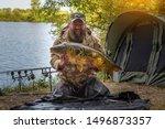 Fishing adventures, carp fishing. Mirror carp (Cyprinus carpio), freshwater fish. Angler with a big carp fishing trophy.Sunrise with a Carp Angler overlooking Lake
