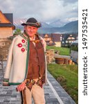 Tatry, Poland - June 03, 2019: An ethnic highlander (Góral)  in traditional goral dress with black hat and shepherd's axe in Polish Tatra mountains. Goral from Zakopane. Eastern Europe - stock photo