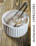 Small photo of sugar tongs in bowl with sugar cubes on wooden table