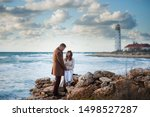 family relationship concept of two young people man and woman conversation on stormy autumn sea shore with beacon