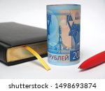 Small photo of Black daily planner, red pen and a banknotes 2000 rubles. Banknotes folded into a tube and stand upright