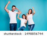 Small photo of Portrait of cheerful family having brunette hair raising fists screaming yeah celebrating victory wearing white t-shirt denim jeans isolated over blue background