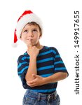 Thoughtful boy in Santa hat, thinking about choice, isolated on white - stock photo