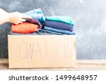 Small photo of hands arranging Donate Box with clothes, donation and charity concept