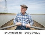 Senior Man Rowing A Boat On A...
