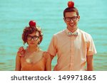 Nerds' honeymoon concept. Portrait of couple of young happy married hipsters in trendy vintage clothes standing together on the beach with apples on their heads. Sunny summer day. Outdoor shot - stock photo