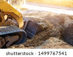 Small photo of Mini bulldozer working with earth while doing landscaping works on construction moving soil