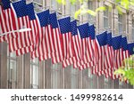 A line of USA flags hanging in the front of the window at Saks 5th Avenue in New York City, NY.