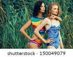 Portrait of two gorgeous young women (girlfriends) in trendy colorful swimsuits posing on the beach. Disco (70s, vintage) style. Arty make-up. Sunny summer day. Copy-space. Outdoor shot - stock photo